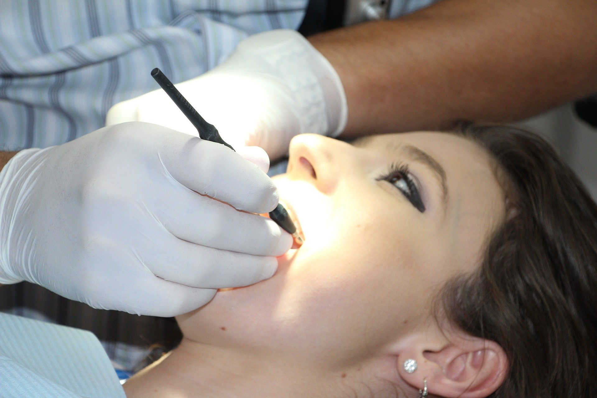 A dentist examining the mouth of the patient